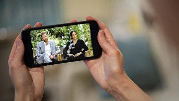 Мужчина смотрит интервью принца Гарри и Меган, герцогини Сассекской на экране смартфона