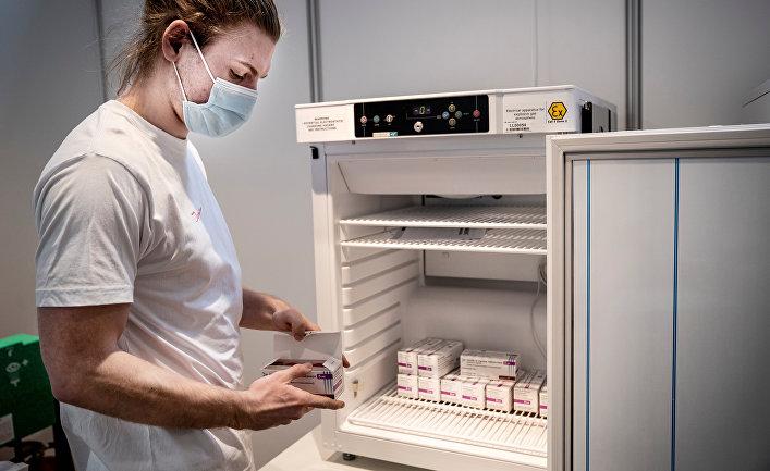 Медработник убирает вакцину от AstraZeneca на хранение в связи с приостановкой вакцинации, Копенгаген, Дания