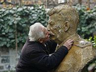 Ушанги Давиташвили целует бюст Иосифа Сталина во дворе своего дома в Тбилиси