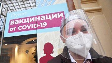 Девушка в защитной маске возле пункта вакцинации от коронавируса в ГУМе в Москве