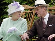 Королева Великобритании Елизавета II и принц Филипп сидя во время музыкального представления в саду аббатства Бери-Сент-Эдмундс