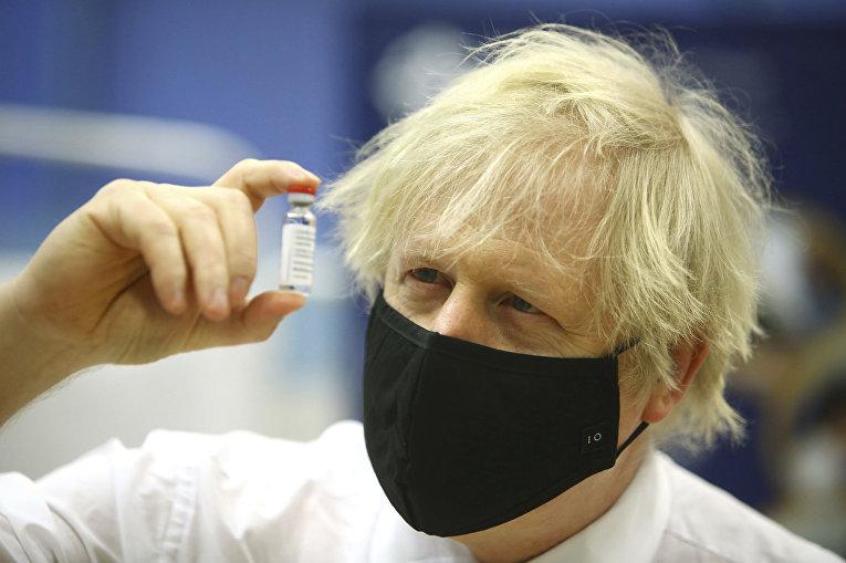Премьер-министр Великобритании Борис Джонсон держит ампулу с вакциной от covid-19 производства AstraZeneca