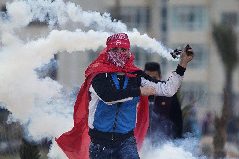 Палестинцы кидают баллончики со слезоточивым газом во время столкновений с израильскими солдатами