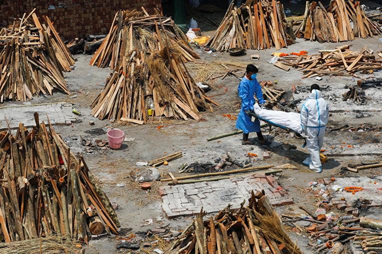 Сотрудники крематория в Нью-Дели, Индия, готовят место для сжигания тел умерших от covid-19