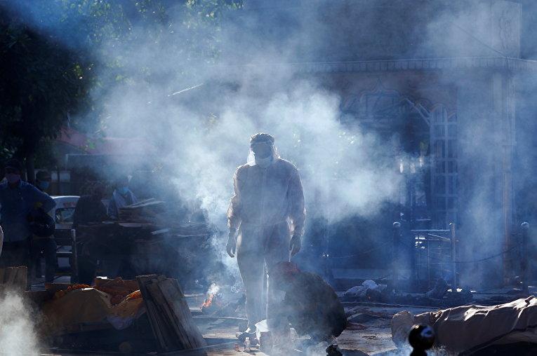 Член семьи человека, скончавшегося от коронавируса. Тело готовят к сжиганию в крематории в Нью-Дели, Индия