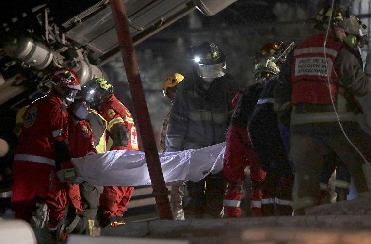 Спасатели выносят тело одной из жертв крушения поезда метро в Мехико, Мексика
