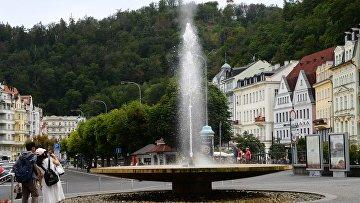 Туристы фотографируют гейзер в городе Карловы Вары