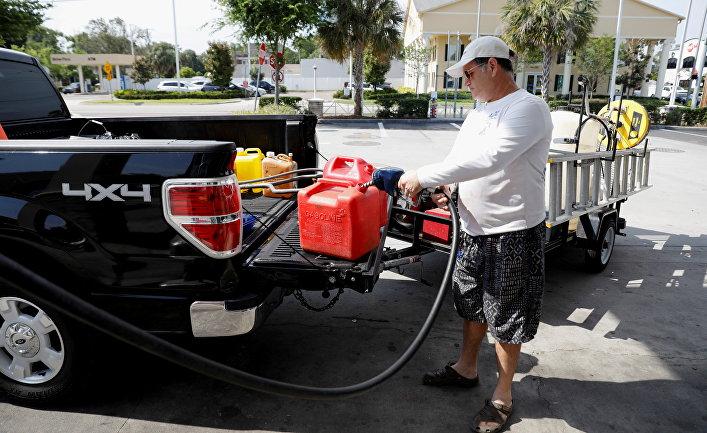 Мужчина наполняет канистры бензином на одной из немногочисленных работающих после кибератаки на трубопровод АЗС во Флориде, США
