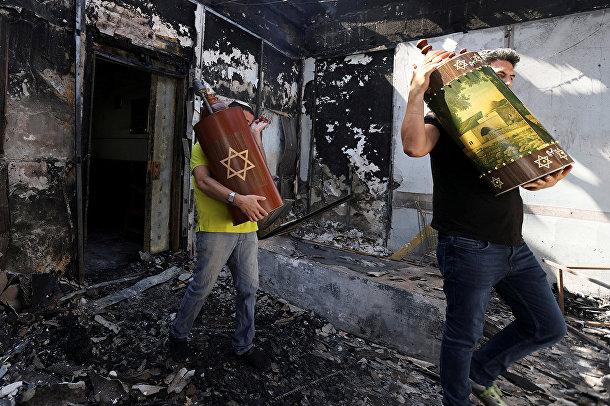 Евреи эвакуируют свитки Торы из сожженной синагоги в Лоде, Израиль