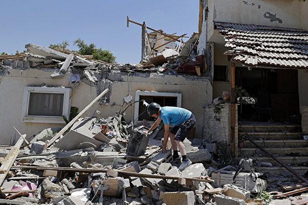 Израильтянин Элиша Голан разбирает завалы в своем доме в городе Йехуд