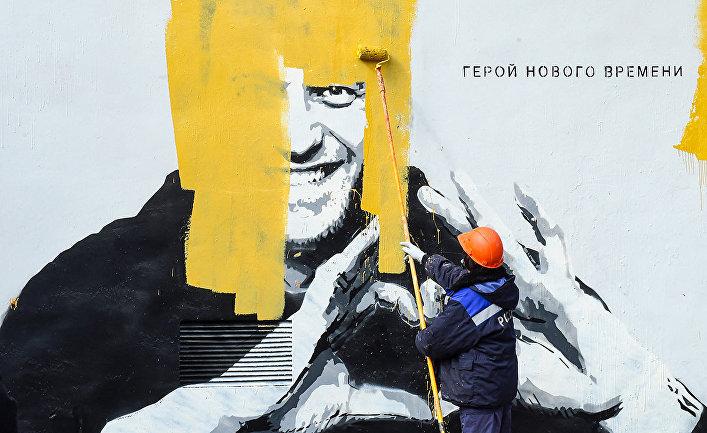 Рабочий закрашивает граффити, изображающее Алексея Навального в Санкт-Петербурге
