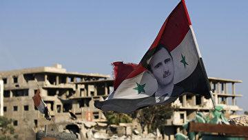 Сирийский национальный флаг с изображением президента Сирии Башара Асада