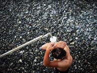 Отдыхающий принемает душ на пляже в городе Сочи