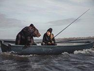 Русская женщина ловит рыбу в компании медведя