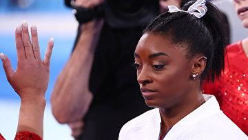 Симона Байлз наблюдает за выступлением американок в финале командного многоборья на Олимпийских играх в Токио